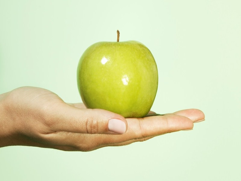 Woman holding Granny Smith apple, close-up
